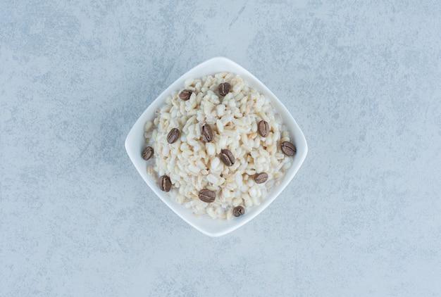 Rijst met melk en koffiebonen op marmer.