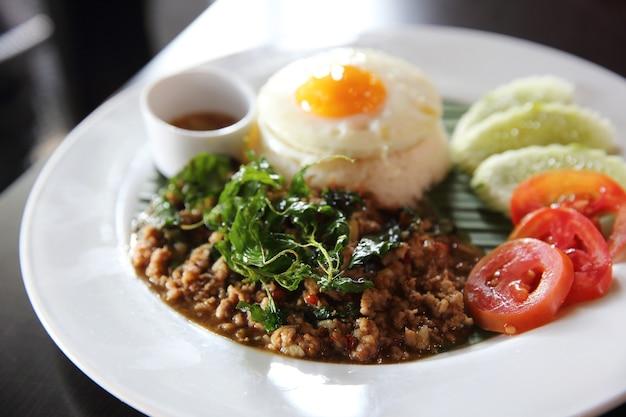 Rijst met roergebakken varkensvlees en basilicum met ei