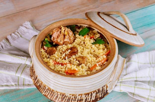 Rijst met rundvlees en groenten in een aarden pot. detailopname. aziatische keuken.