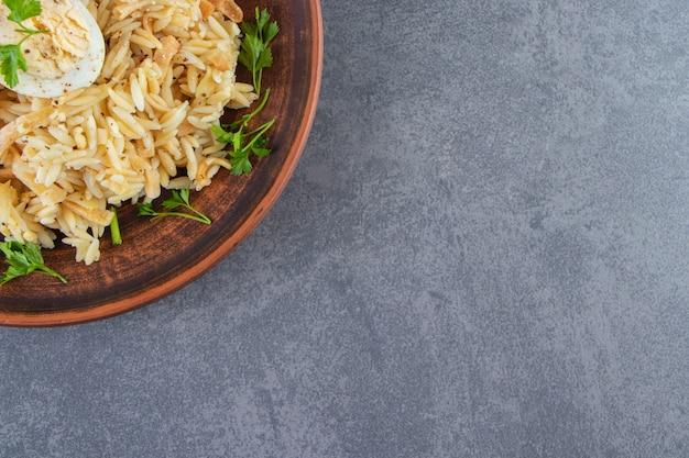 Rijst met vermicelli op een bord naast groenten, op de blauwe achtergrond.