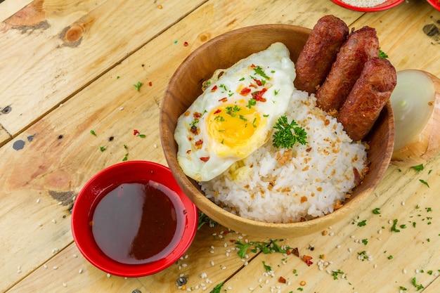 Rijst, omelet en worstjes met kruiden geserveerd in een kom en in de buurt