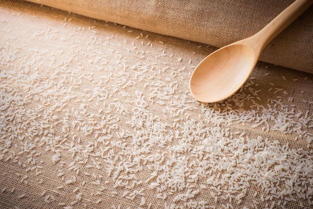 Rijst op jute en houten lepelgebruik voor achtergrond