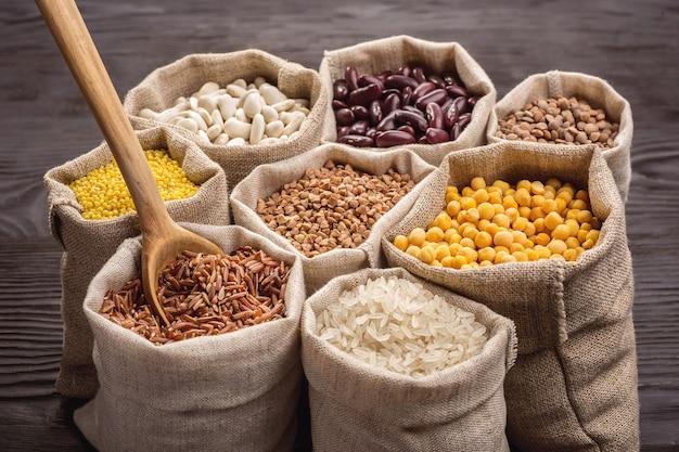 Rijst, peulvruchten en granen in zakken op donkere houten tafel.