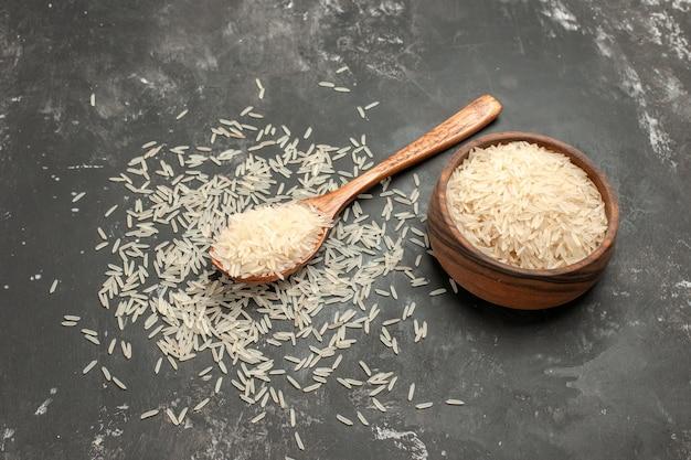 Rijst rijst in de houten kom en lepel op de donkere tafel