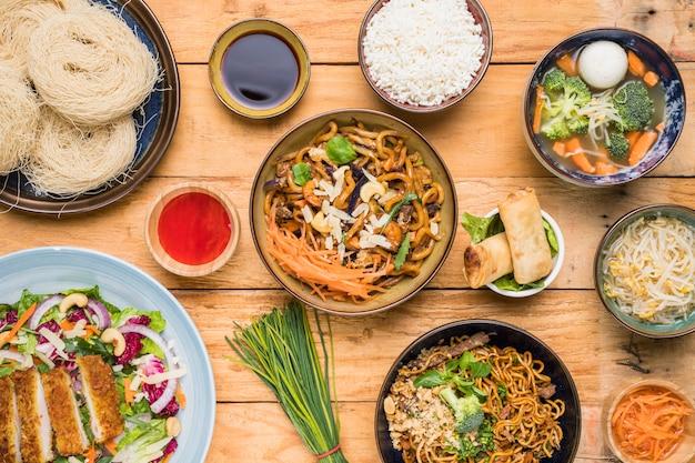 Rijst; udon noedels; loempia's; bieslook; spruiten bonen; vis bal soep en salade op tafel