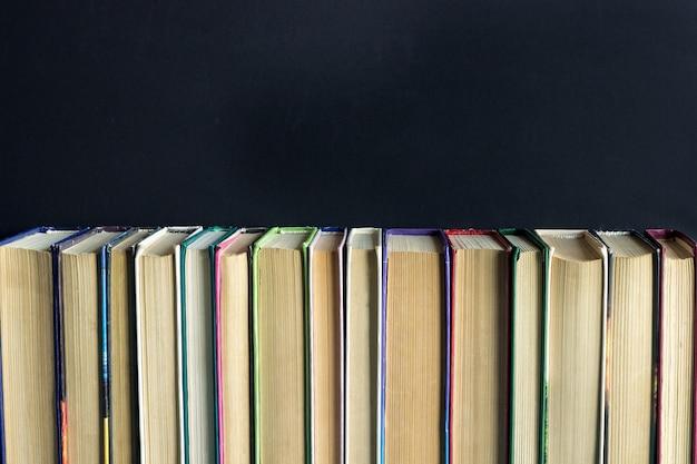 Rijstapel oude boeken op zwart schoolbord als achtergrond