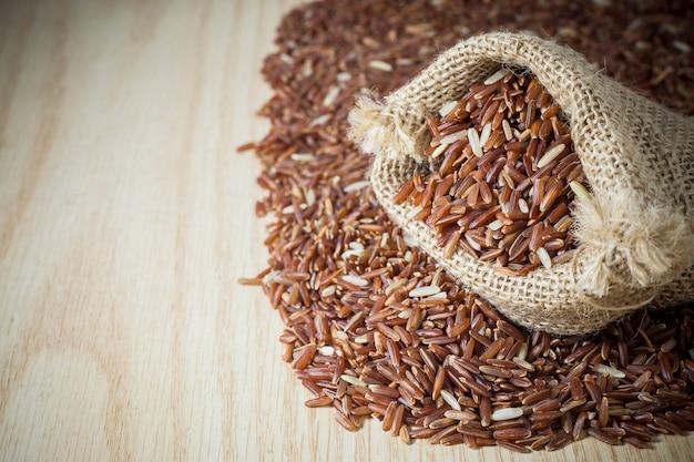 Rijstbes in een zak op een houten achtergrond.
