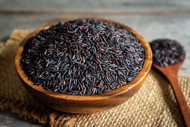 Rijstbes in houten kom met lepel op houten lijst
