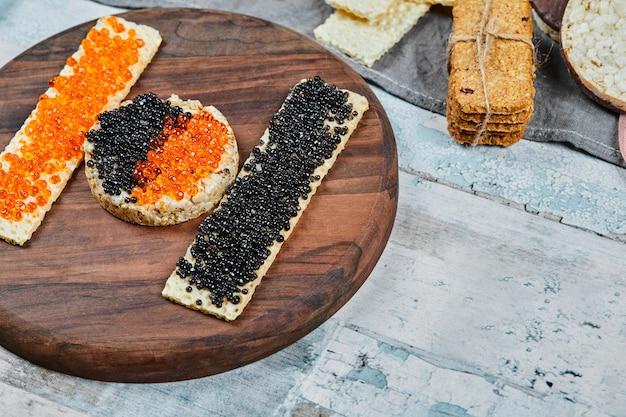 Rijstcrackers met rode en zwarte kaviaar op houten plaat.