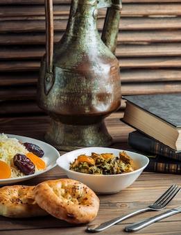 Rijstgarnituur, tandirbroodjes en groene salade op een tafel