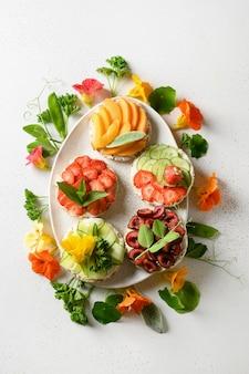 Rijstknäckebröd met decoratieve toppings van fruit en groenten.
