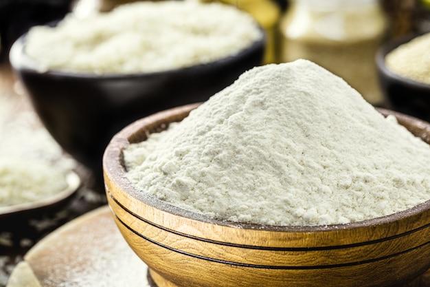 Rijstmeel in een geblazen houten pot, glutenvrij en volkoren ingrediënt