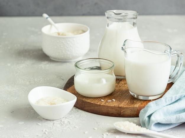 Rijstmelk in kannen en rijst in witte keramische kommen en lepel op een lichtgrijze steen.