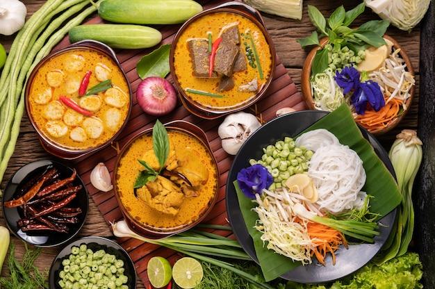 Rijstnoedels in een kom currypasta met chili, komkommer, kousenband, limoen, knoflook en bosui