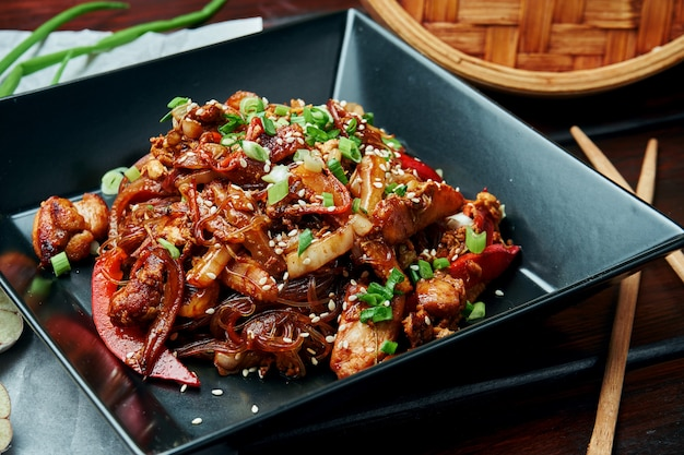 Rijstnoedels met baby maïs, paprika, uien, wortelen en kip gebakken op een wok met teriyaki saus in zwarte plaat op houten tafel. lekker aziatisch straatvoedsel