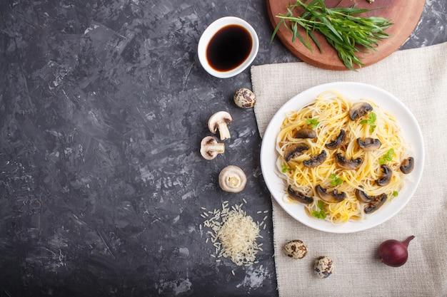 Rijstnoedels met champignonspaddestoelen op een zwart beton. bovenaanzicht