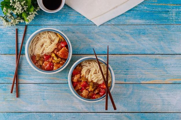 Rijstnoedels met gewokte kip en groenten in kommen en eetstokjes