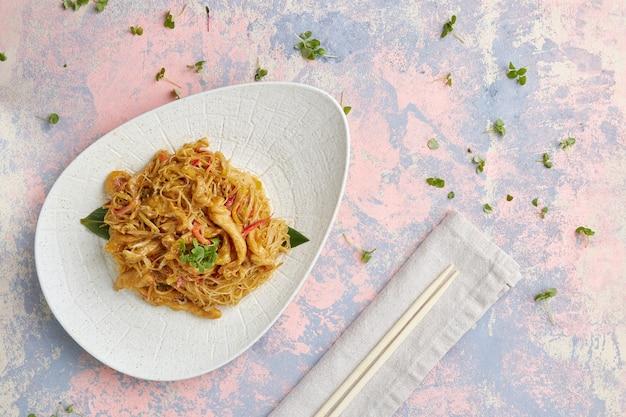 Rijstnoedels met kip, kerriesaus, bovenkant, gekleurde achtergrond