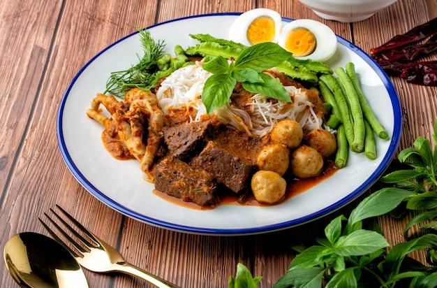 Rijstnoedels met viscurry saus, top met gehaktbal, kippenbloedblokjes, kippenpootjes, gekookt ei en veel groente. thais eten, thais noemen het