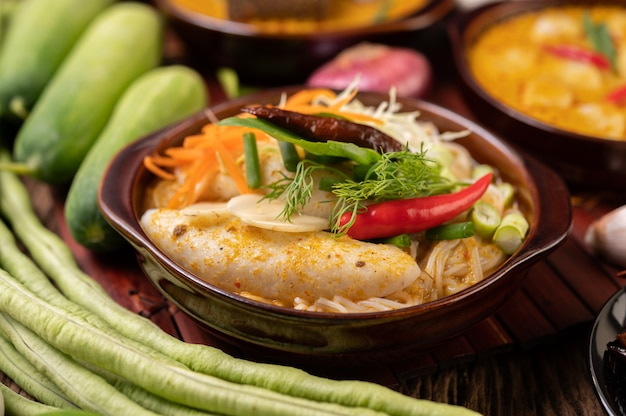 Rijstnoedels, rode curry met gehaktballetjes, met gedroogde pepers, basilicum, komkommer en kousenband