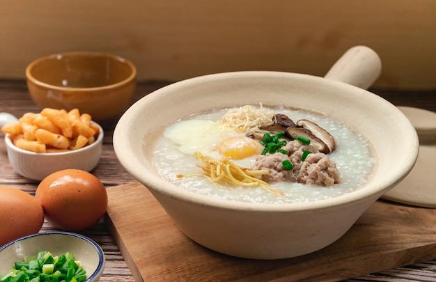 Rijstpap met zachtgekookt ei en fijngehakt ei in witte kleipot bijgerecht met knapperige patongo gefrituurde deegstok thais ontbijt