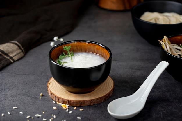 Rijstsoep in een zwarte kom op een houten steun en een witte lepel