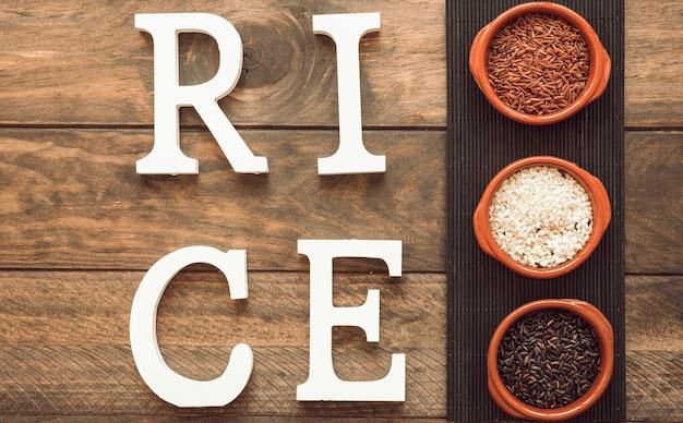 Rijsttekst met kommen rijstkorrels op placemat over de houten lijst