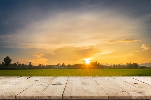 Rijstveldzonsondergang en lege houten lijst voor productvertoning en montering.