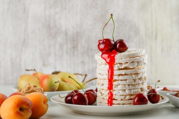 Rijstwafels in een bord met kersen, noten, peren, abrikozen, pindakaas