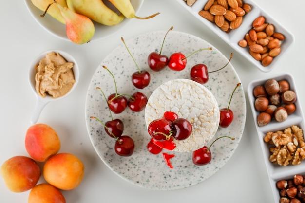 Rijstwafels met kersen, noten, peer, abrikoos, pindakaas in een plat op witte achtergrond, bovenaanzicht.