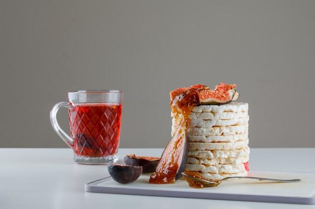 Rijstwafels met vijgen, jam, thee, theelepel op snijplank op wit en grijs,