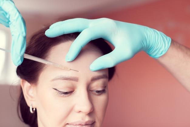Rimpels in het gezicht op het voorhoofd gladstrijken met botox-injecties