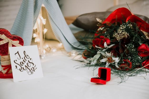 Ring en bloemen in de buurt van stapel geschenken