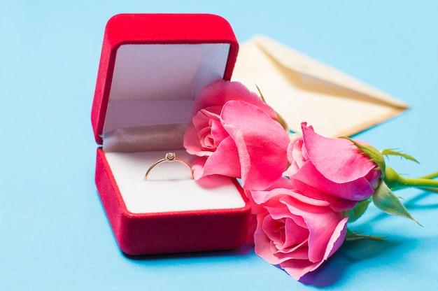 Ring in een doos met een envelop en rozen op een blauwe achtergrond