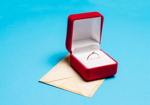 Ring in een doos met een envelop op een blauw