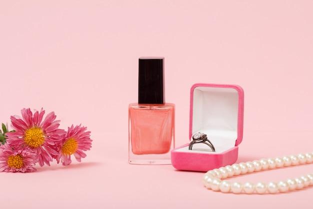 Ring in een doos, nagellak, kralen en bloemen op een roze achtergrond. vrouwen sieraden, cosmetica en accessoires.