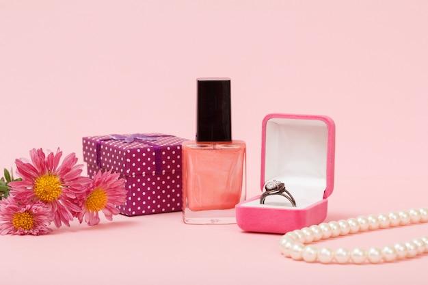 Ring in een doos, nagellak, kralen, geschenkdoos en bloemen op een roze achtergrond. vrouwen sieraden, cosmetica en accessoires.
