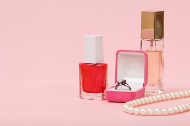 Ring in een doos, nagellak, parfum en kralen op een roze achtergrond. vrouwen sieraden, cosmetica en accessoires.