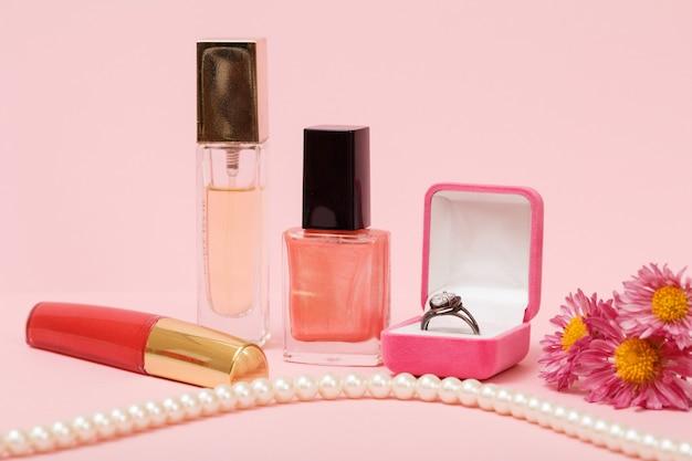 Ring in een doos, nagellak, parfum, lippenstift, kralen en bloemen op een roze achtergrond. vrouwen sieraden, cosmetica en accessoires.