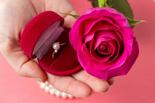 Ring in rode doos en bloem in handen. valentijnsdag geschenk