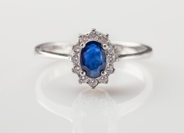 Ring van de juwelier met donkerblauwe saffier en briljanten op een witte achtergrond met reflectie