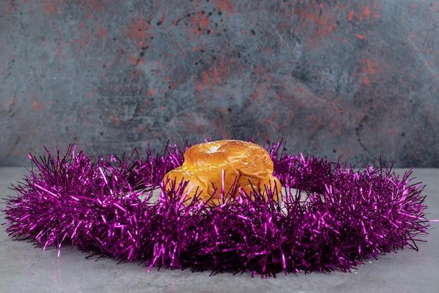 Ring van paars klatergoud rond een klein broodje op marmeren tafel.