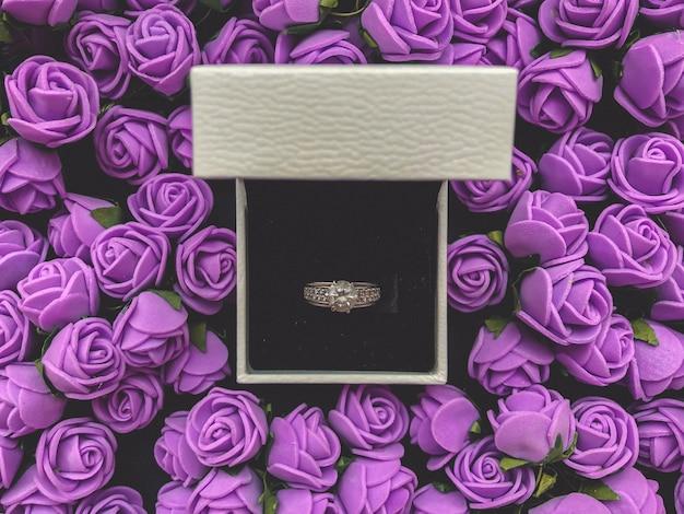 Ring voor huwelijksaanzoek versierd met decoratieve bloemen. valentijnsdag achtergrond.
