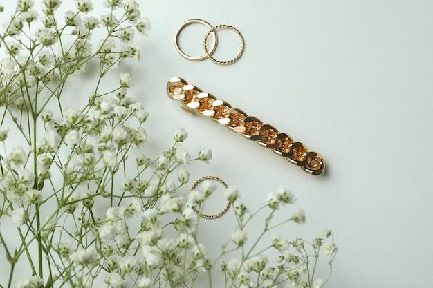 Ringen, haarklem en gipskruid op witte achtergrond
