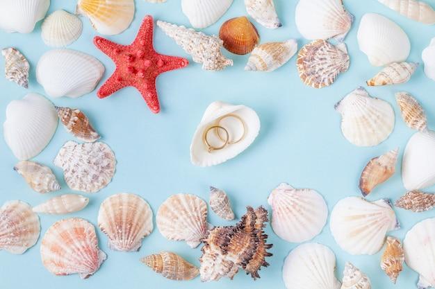 Ringen op een schaal op een blauwe zomer achtergrond met verschillende schelpen en zeesterren