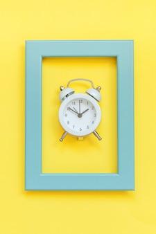 Ringing twin bell vintage wekker in blauw frame geïsoleerd op gele kleurrijke trendy achtergrond
