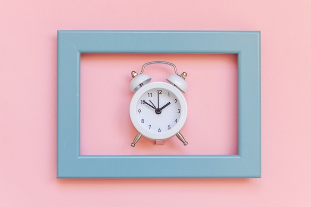 Ringing twin bell vintage wekker in blauw frame geïsoleerd op roze pastel kleurrijke trendy achtergrond