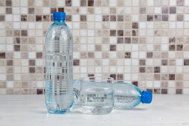 Rinkend waterflessen en glas met water op witte keukentafel