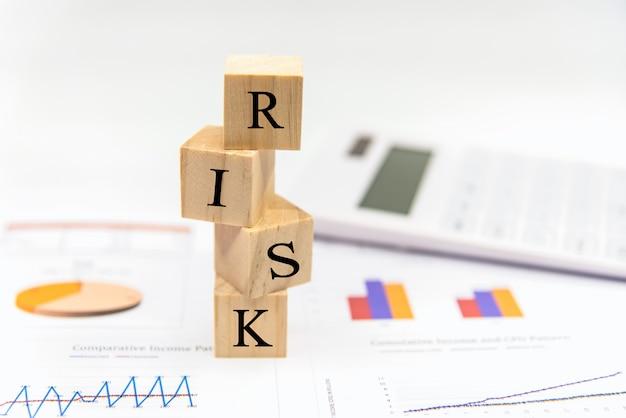 Risico bij bedrijfsinvesteringen. woordrisicowit in het houtblok op papier analyseert financiële grafiek. investeringsconcept.