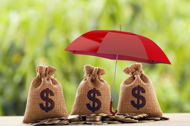 Risicobescherming, vermogensbeheer en langetermijninvesteringen in geld, financieel concept: munten regelen en zak in amerikaanse dollar onder de rode paraplu. beeldt activabeveiliging af voor duurzame groei.